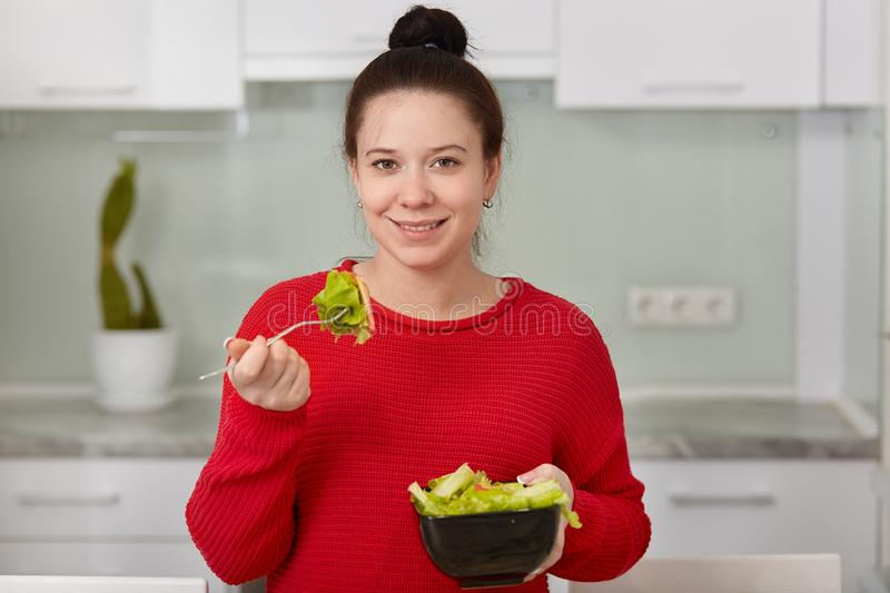 Shot of brunette woman with healthy skin, charming smile, eats delicious vegetarian salad from bowl, keeps to diet, wears red. Sweater, poses against kitchen royalty free stock photography