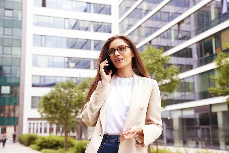 Young businesswoman making a call while walking on the street stock images