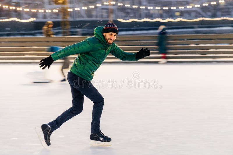 Shot of cheerful male has fun outdoor, skates on ice ring, enjoy stock images