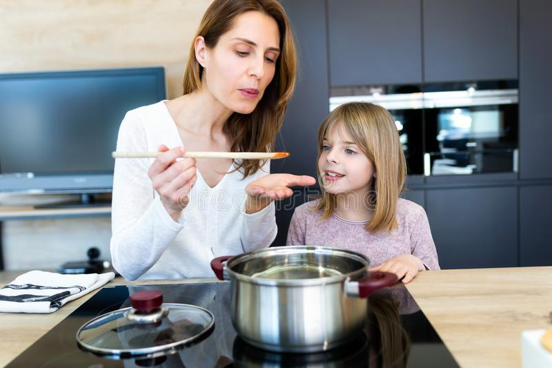 Cheerful young woman giving his little daughter to try the food she is preparing in the kitchen at home stock photos