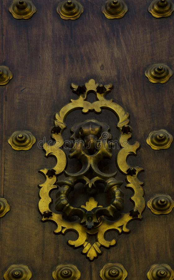 Golden iron knockers with bird head. Shot in color detail on the architecture of this historic building church. Set in Cordoba, Andalucia, Spain, Europe stock image
