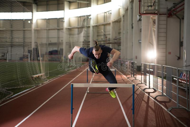Concentrated male track and field athlete jumping over the hurdle royalty free stock images