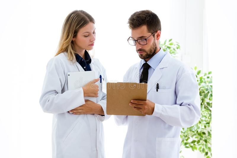 Confident female and male doctors writing information in folder in medical consultation. stock image