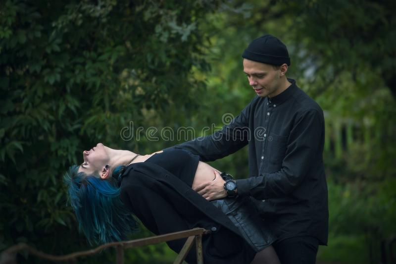 Shot of a dangerous man grabbing a scared blue hair woman stock photo