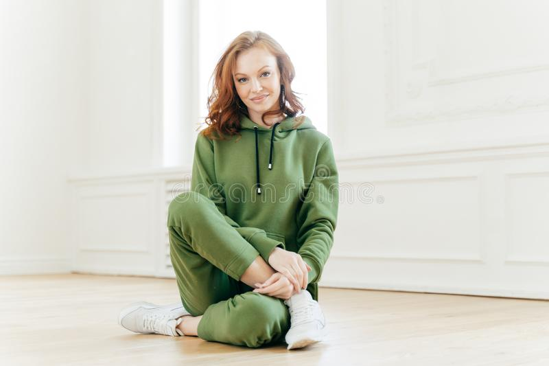 Shot of delighted European red haired female stretches legs, prepares for jogging exercise, dressed in tracksuit, has healthy. Fresh skin, slim body shape stock image