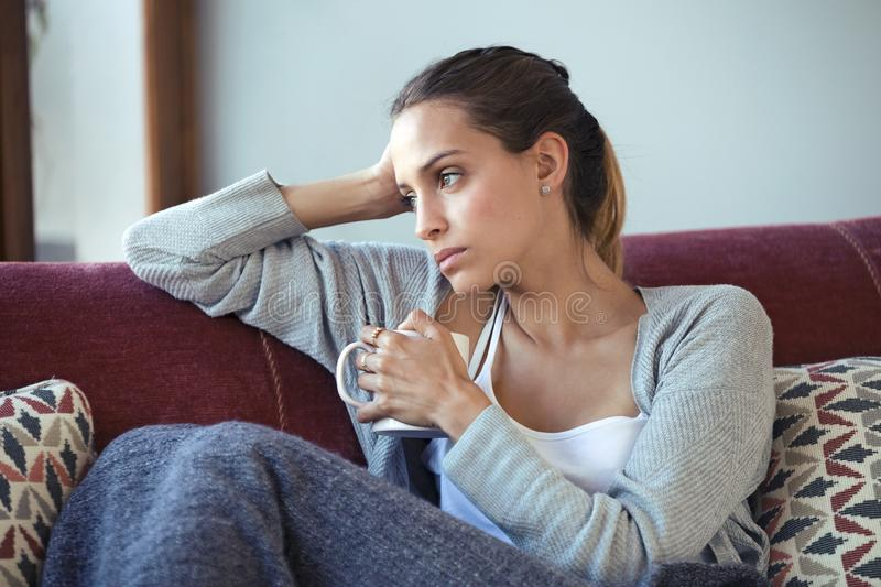 Depressed young woman thinking about her problems while drinking coffee on sofa at home stock images