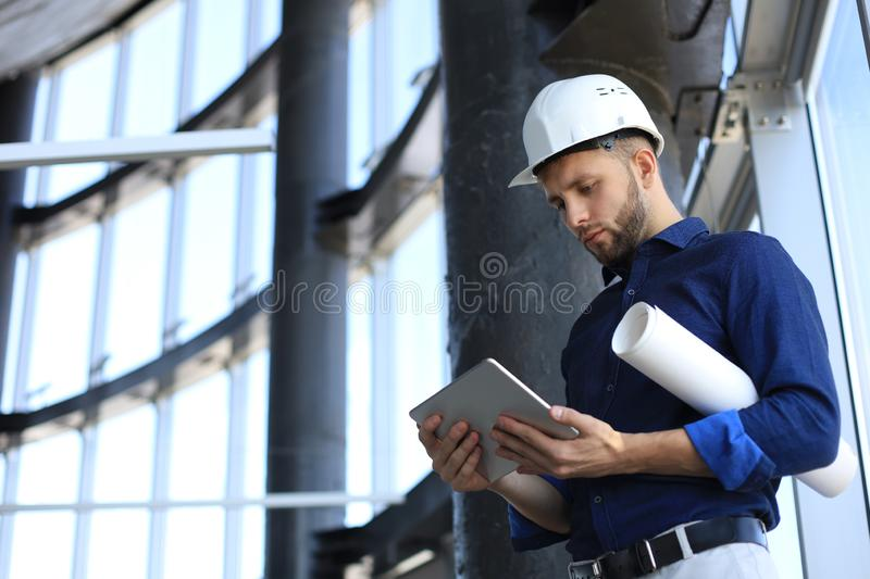 Shot of a engineer using a digital tablet on a construction site. This software help me to keep track of everything stock photography