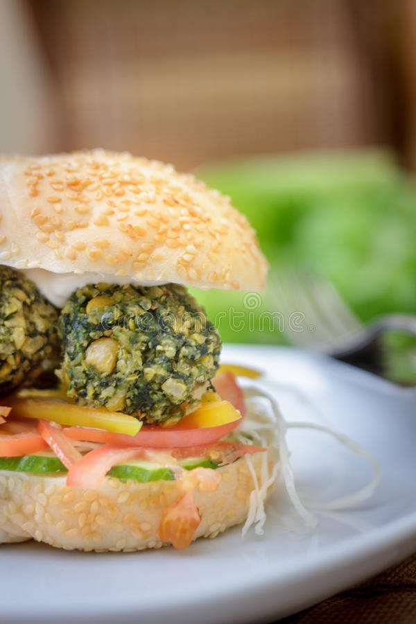 Shot of falafel burger whith the fresh vegetables and falafel balls inside it. stock photos