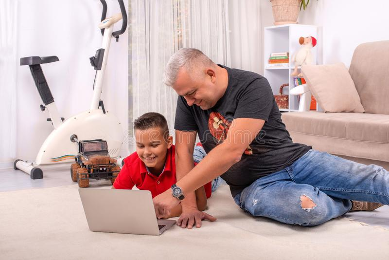Shot of a father and son browsing on a laptop together  sitting on the floor in their home royalty free stock images