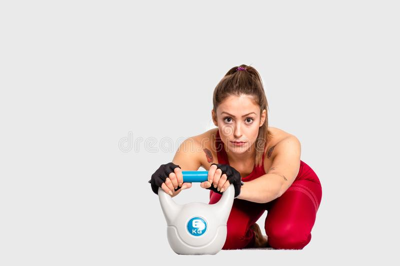 Shot of female bodybuilder in sportswear doing crossfit workout with kettle bell on white background Confident looking forw- Image royalty free stock photo