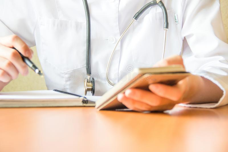 Shot of female doctor`s hands using smart phone. Professional is scrolling and searching info.  royalty free stock photos