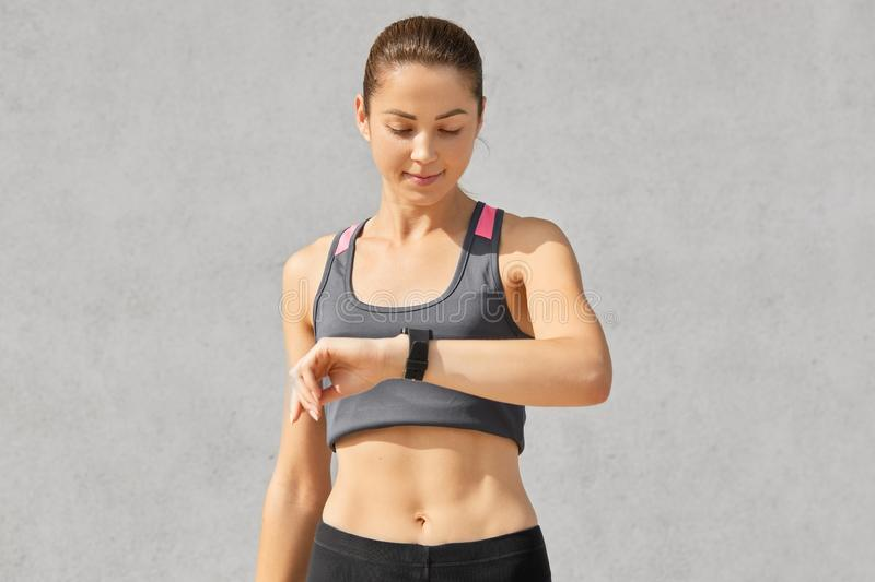 Shot of fitness lady or jogger looks attentively at smart watch, checks pulse and counts calories, has healthy lifestyle, goes in stock images