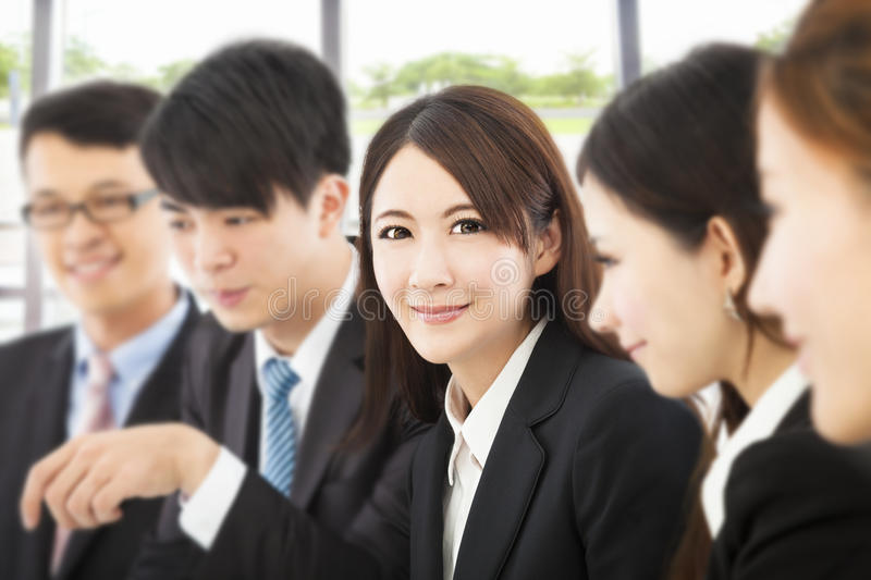 Shot of focus on young business woman with colleagues royalty free stock images
