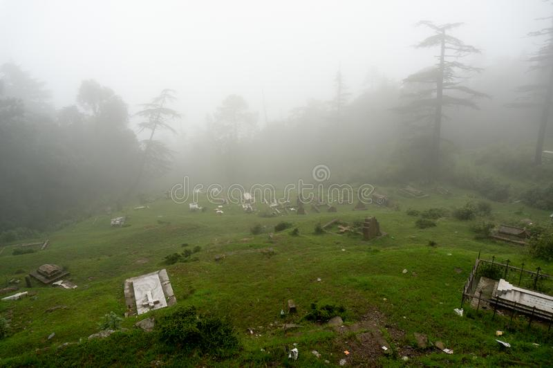 Shot of a foggy graveyard on a hill slope with trees in the background fading into the distance. stock photography