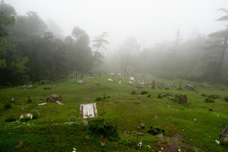 Shot of a foggy graveyard on a hill slope with trees in the background fading into the distance. royalty free stock photo