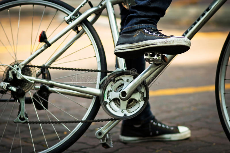 Shot of the foot on pedal of bicycle. Shot of the foot on pedal of gray bicycle stock photography