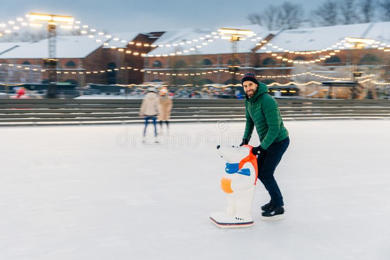 Shot of glad bearded male spends time outdoor on fresh air, enjoys frosty winter weather, goes skating on ice ring, uses skae aid royalty free stock images