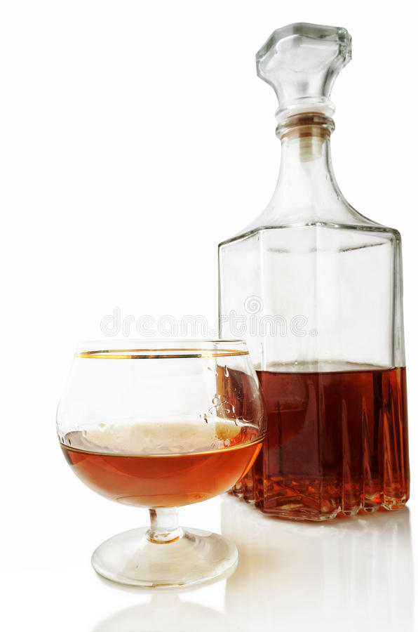 Shot glass and decanter with alcohol on a white background with stock photo