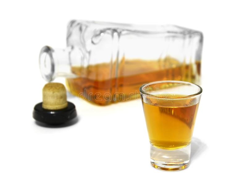 Shot glass of delicious whiskey and open bottle royalty free stock images