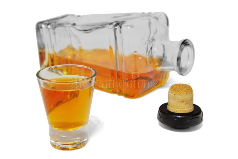 Shot glass of delicious whiskey and open bottle stock image