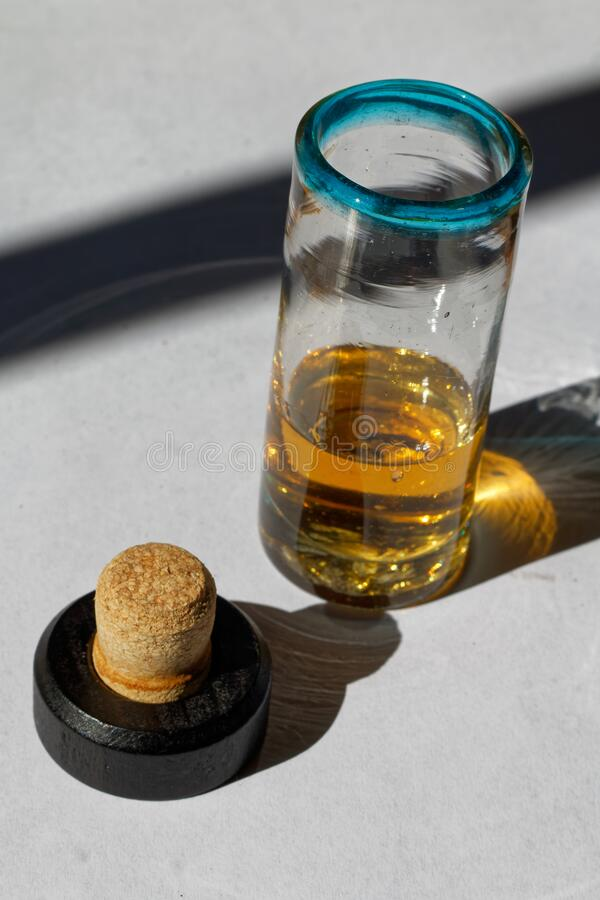 A shot glass with tequila. Mexican handmade shot glass with tequila anejo. Bottle cap with cork royalty free stock images