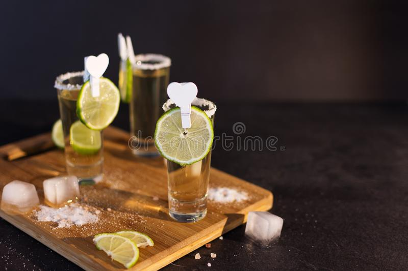 Shot glasses of gold tequila with a rim of salt, and lime slices royalty free stock images