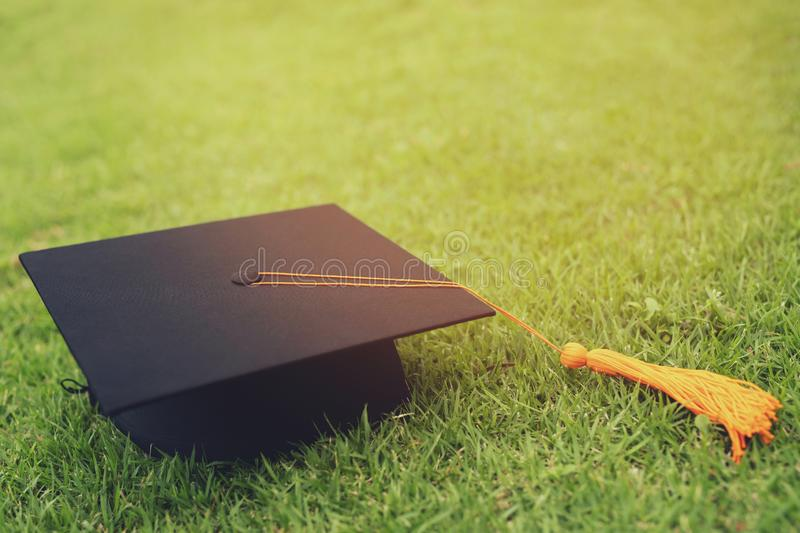 Shot of graduation hat on the grass, concept during commencement success graduates of the university, education congratulation. Le. Shot of graduation hat on the stock image