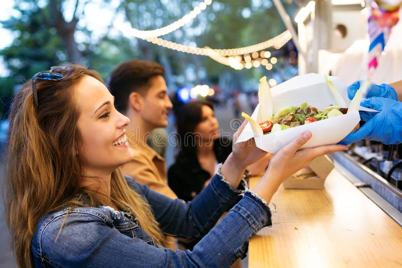 Group of attractive young friends choosing and buying different types of fast food in eat market in the street. Shot of group of attractive young friends royalty free stock photo