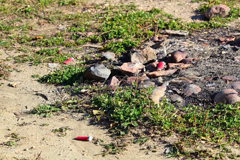 Shot gun shells around a hunting campfire pit.  stock photography