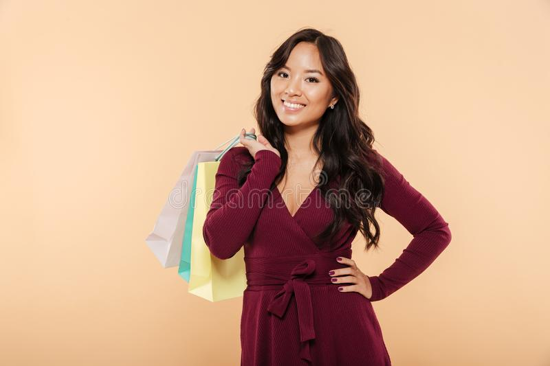 Shot of happy asian lady in maroon dress posing over beige background holding packs with purchases after shopping on sale day. Shot of happy asian lady in maroon stock photo