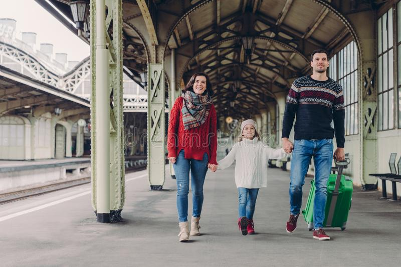 Shot of happy family going to have nice trip during holidays, carry bag, walk on railways station platform, being in good mood. stock photography