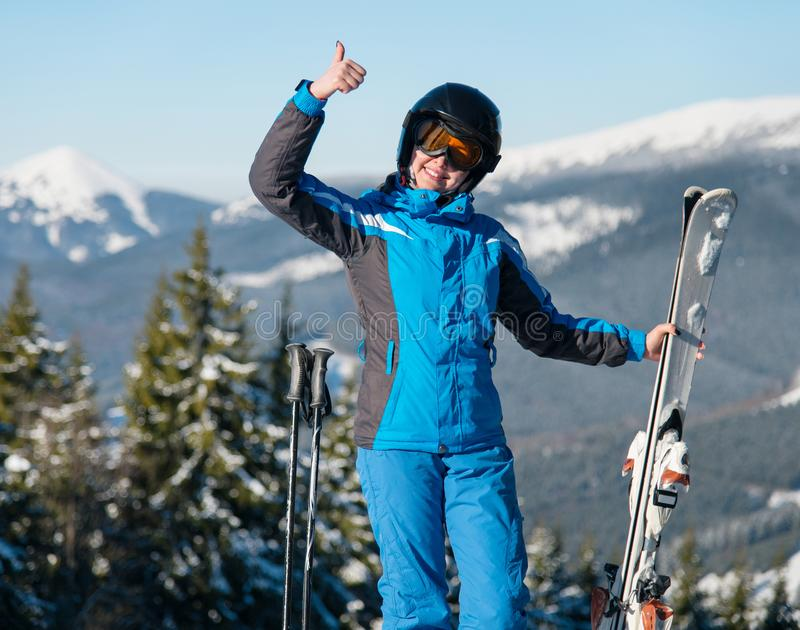 Shot of a happy female wearing skiing gear smiling showing thumbs up posing in the mountains stock photo