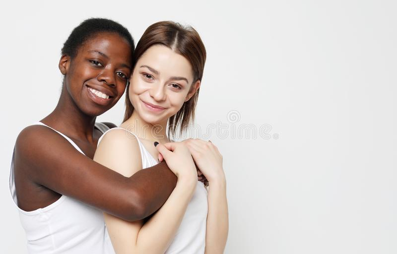 Shot of happy interracial homosexual couple hugging.African-American girl and her charming Caucasian girlfriend. royalty free stock image