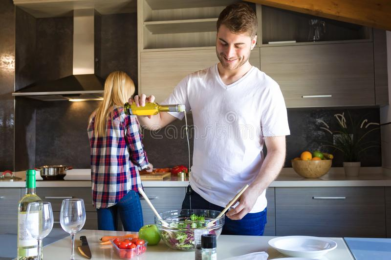 Happy young couple cooking together in the kitchen at home. royalty free stock photo
