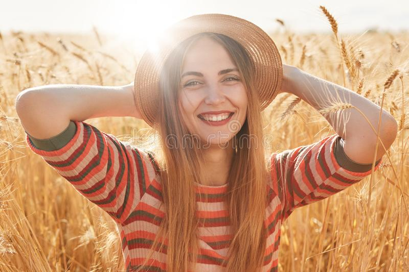 Shot of happy young woman in striped dress and sun hat enjoying sun on wheat field, keeps her hands on head, looking smilling at. Camera, relaxing in open air stock photo
