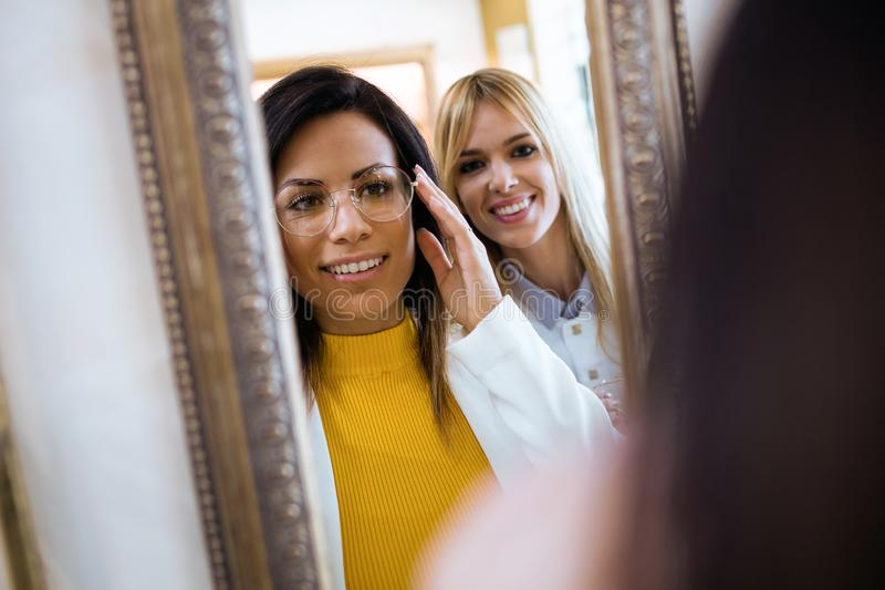 Happy young woman choosing eyeglasses and looking at the mirror while attractive young oculist standing near in optic shop royalty free stock images