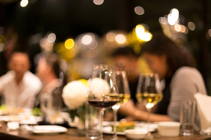 Group of friends having a dinner and wine in blurred conceptaul stock images