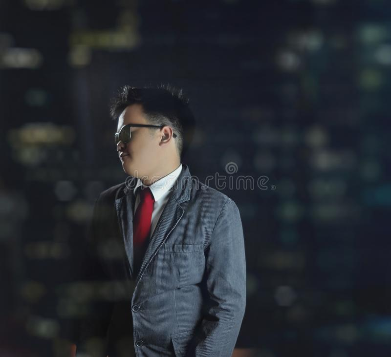 Handsome young man in suit and red tie and sunglasses looking away. stock image