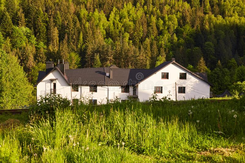 Shot of large white house in bottom of mountains, house situated near forest, guest house in mountains area, place for having rest stock images