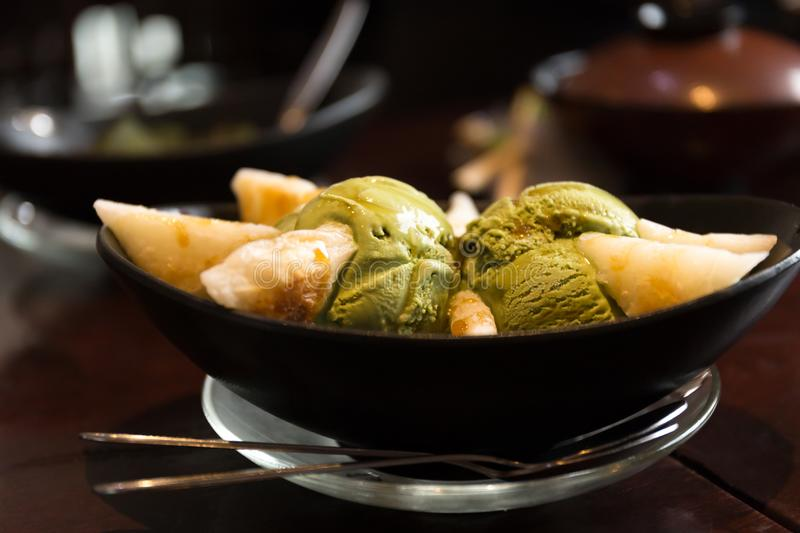 Shot in low light high iso Matcha ice cream scoop in bowl. On wooden table royalty free stock photography