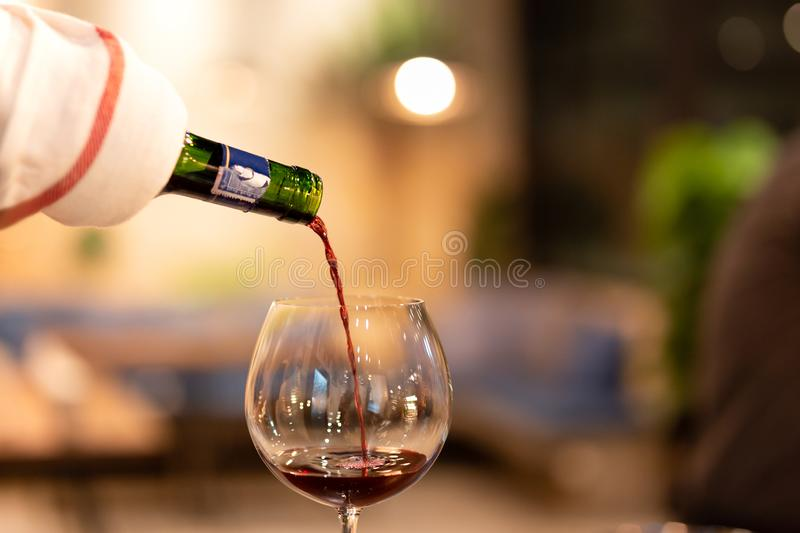 Shot in low light and high iso red wine pouring down from wine bottle. Shot in low light and high iso red wine pouring down from wine bottle royalty free stock images