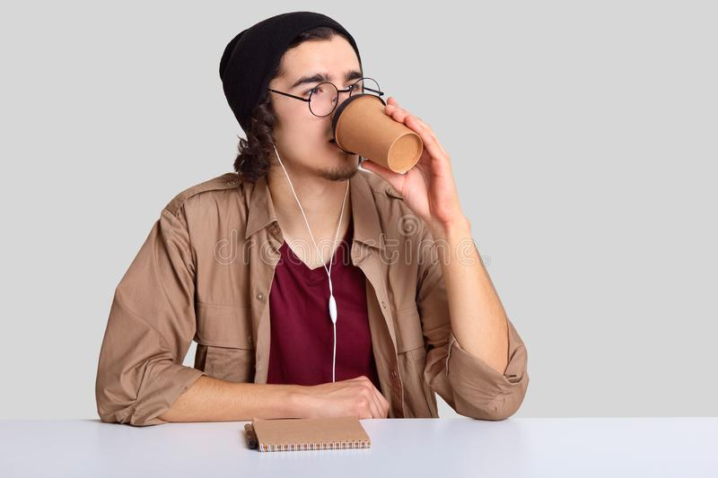 Shot of male teenager has coffee break after work, holds paper cup with aromatic beverage, dressed in black hat and beige shirt, stock photo