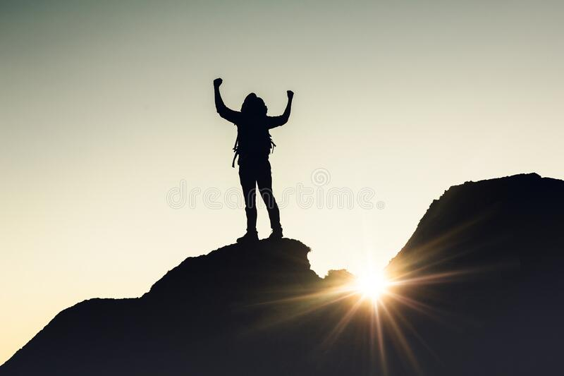 Man with arms raised at sunset royalty free stock images