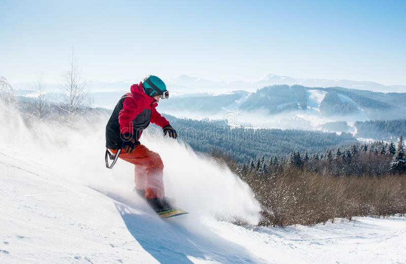 Professional snowboarder riding in the mountains. Shot of a man snowboarder riding on the snowy slope at winter ski resort in the mountains, wearing snowboarding stock image