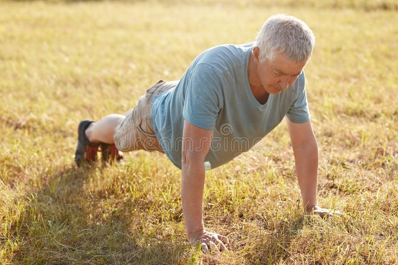 Shot of mature male does push ups on green grass, being flexible, warms up before jogging, enjoys fresh air and beautiful nature,. Cares of body. Sporty mood royalty free stock images