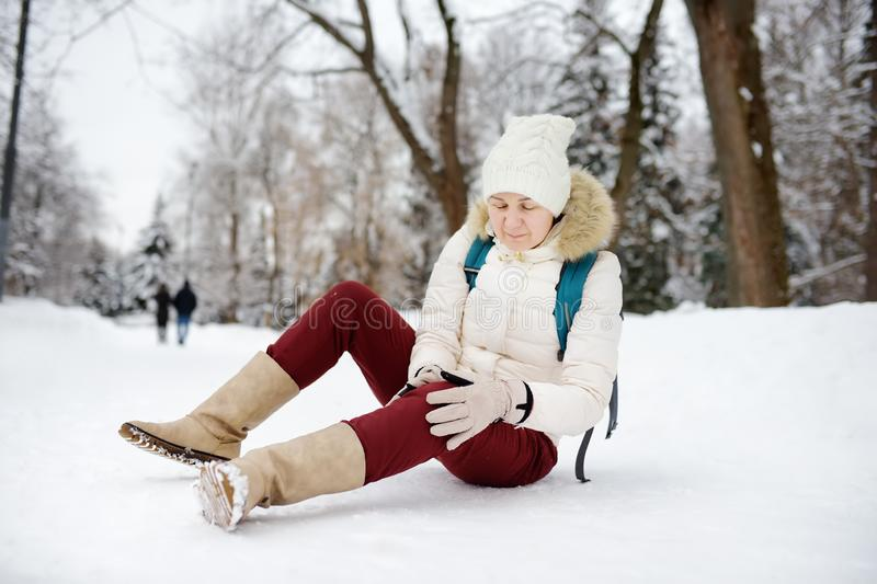 Shot of person during falling in snowy winter park. Woman slip on the icy path, fell, injury knee and sitting in the snow. Danger of season trauma royalty free stock photo