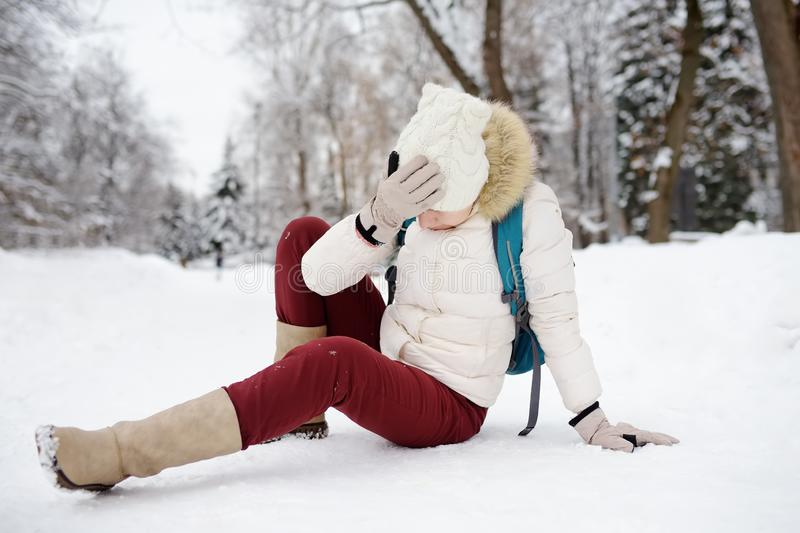 Shot of person during falling in snowy winter park. Woman slip on the icy path, fell and lies. Danger of season trauma royalty free stock photo