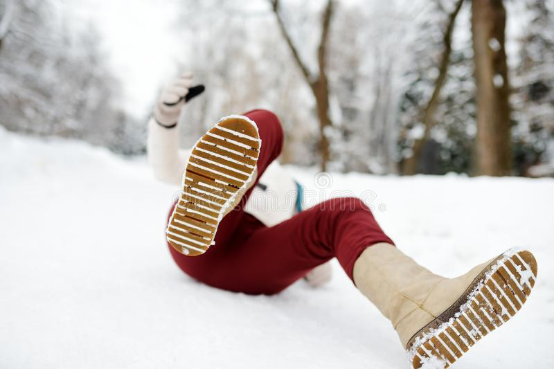 Shot of person during falling in snowy winter park. Woman slip on the icy path, fell and lies. Danger of season trauma stock photo