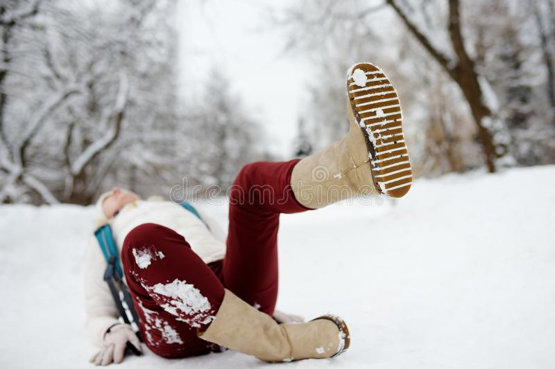 Shot of person during falling in snowy winter park. Woman slip on the icy path, fell and lies. Danger of season trauma stock images