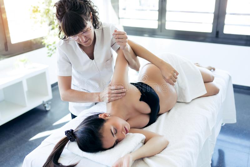 Physical therapist massaging pregnant woman`s arm in spa center royalty free stock photo